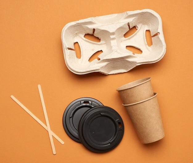 Одноразовые бумажные стаканчики из коричневой крафт-бумаги и держатели из переработанной бумаги