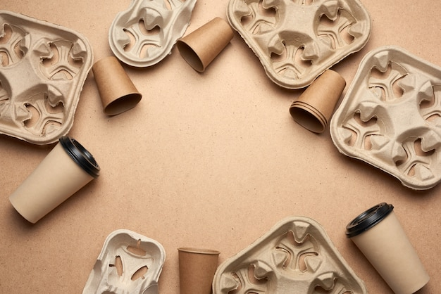 Disposable paper cups from brown craft paper and recycled paper holders on a brown wooden background