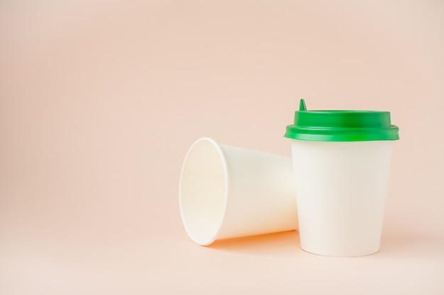 薄いピンクの背景にプラスチック製のふた付きの使い捨て紙コップ。