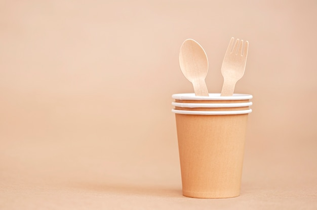 Disposable paper cups with wooden fork and spoon on paper background