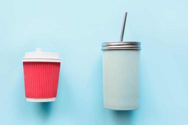 Disposable paper red cup and reusable mug on blue.