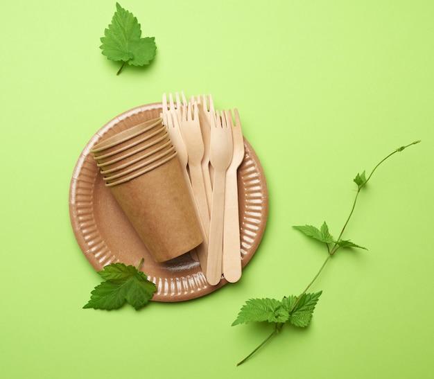 Одноразовая бумажная посуда из коричневой крафт-бумаги и переработанных материалов на зеленом фоне, концепция отбраковки пластика, ноль отходов