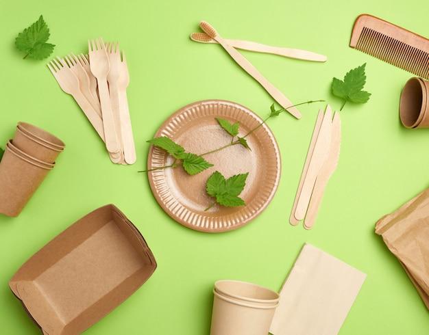 Одноразовая бумажная посуда из коричневой крафт-бумаги и переработанных материалов на зеленом фоне