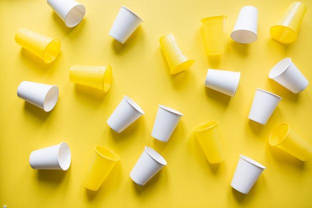 Одноразовая посуда для пикника для утилизации на желтый. окружающей среды экологически дружественных отбрасывается пластиковый мусор для рециркуляции концепции. вид сверху. квартира лежала.