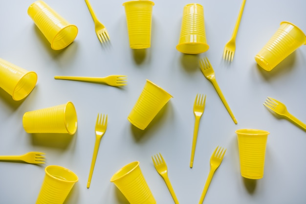 Disposable picnic yellow utensils on grey. flat lay.