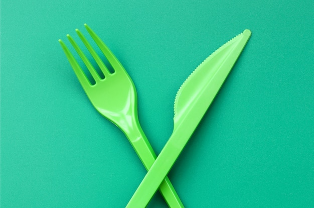 Disposable plastic cutlery green. plastic fork and knife lie on a green background surface
