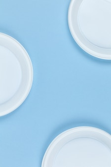 Disposable plastic dishes, plates, blue background, copy space