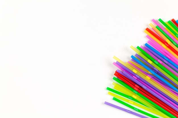 Disposable plastic multicoloured tubules for drinks located in right corner of image on white background, copy space.