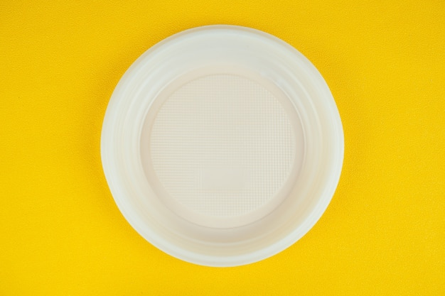 黄色の背景に使い捨てプラスチックプレート