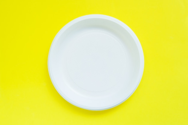 Disposable plastic plates on bright yellow table with copy space.