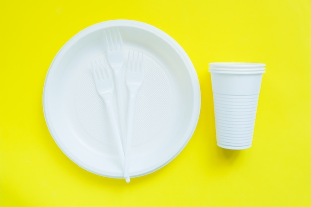Disposable plastic tableware on bright yellow surface