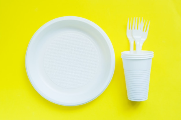 Disposable plastic tableware on bright yellow table with copy space.