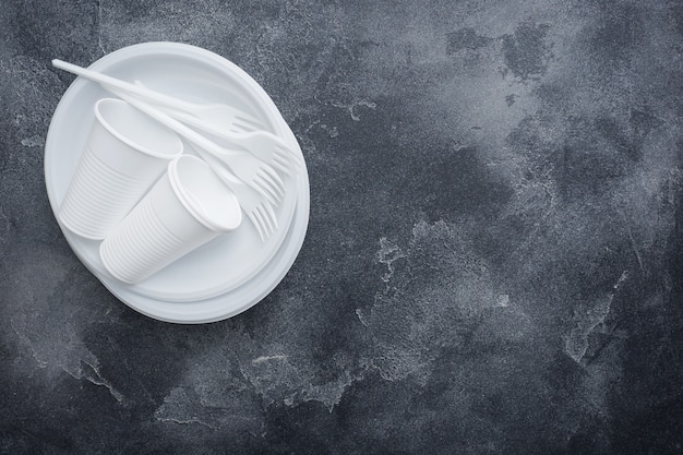 Disposable plastic tableware on dark background with copy space.