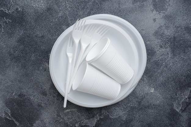 Disposable plastic tableware on dark table with copy space.