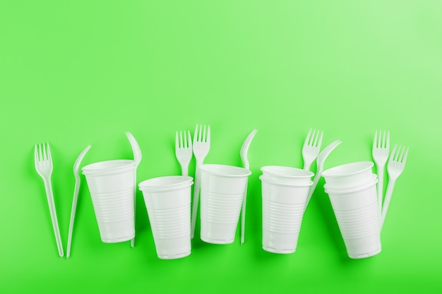 Disposable plastic tableware on a green surface