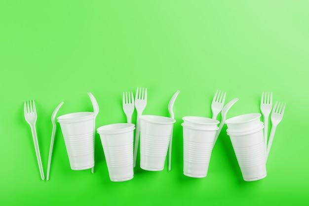 緑の表面に使い捨てのプラスチック製食器