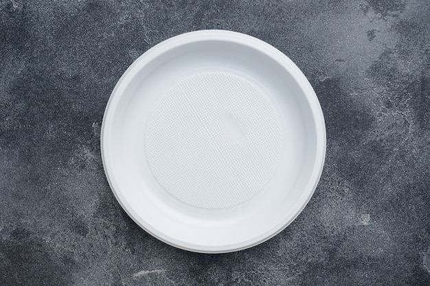 Disposable plastic tableware plates on dark table with copy space.