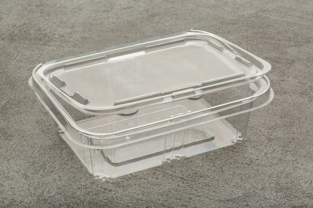 Disposable plastic transparent lunch box on a gray concrete table.