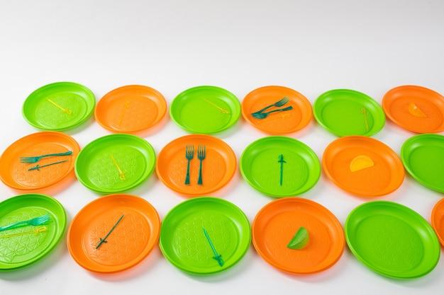 使い捨てプレート。カラフルで明るいプラスチックプレートが離れており、非体系的な消費の例としてフォークと串があります