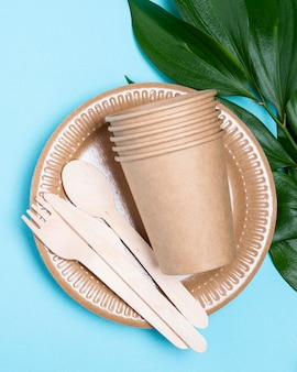 Disposable plates with cups and cutlery flat lay