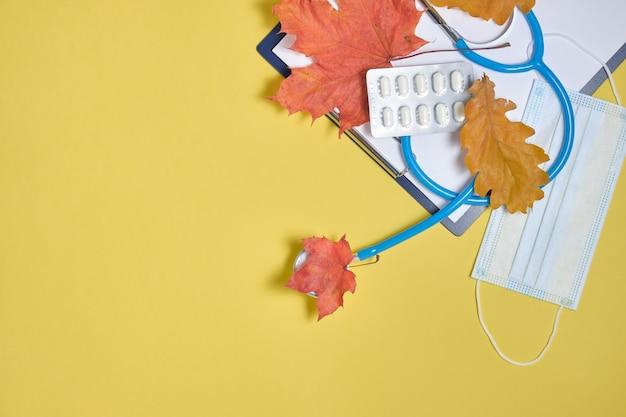 Одноразовые защитные медицинские маски и стетоскоп и осенние кленовые листья