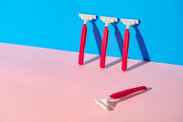 青とピンクの背景に使い捨てカミソリ、スタジオショット