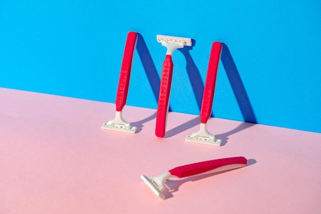 青とピンクの背景に使い捨てカミソリ