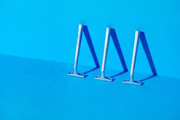 青い背景、スタジオショット、コピースペースの使い捨てカミソリ