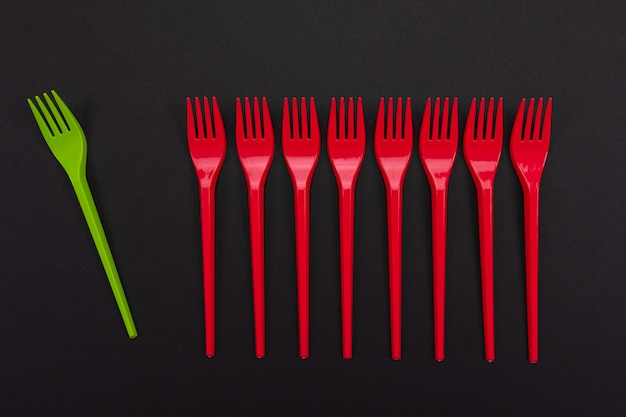 Одноразовые красные и зеленые пластиковые вилки, изолированных на фоне