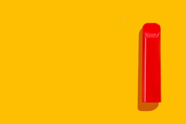 Одноразовые красные электронные сигареты на желтом фоне