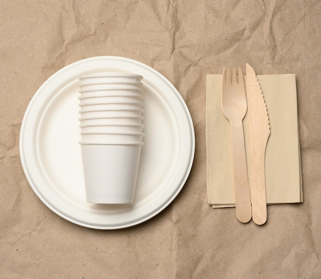 Disposable round white paper plates and cups on brown paper background, top view, zero waste