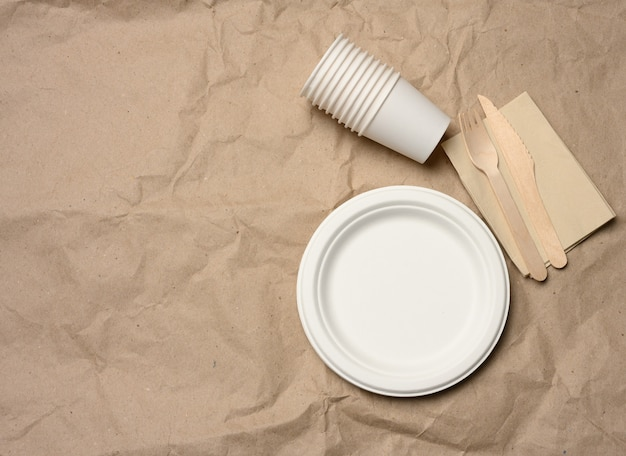 Disposable round white paper plates and cups on brown paper, top view, zero waste