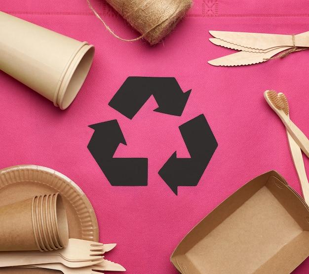Одноразовая посуда из коричневой крафт-бумаги на розовом фоне