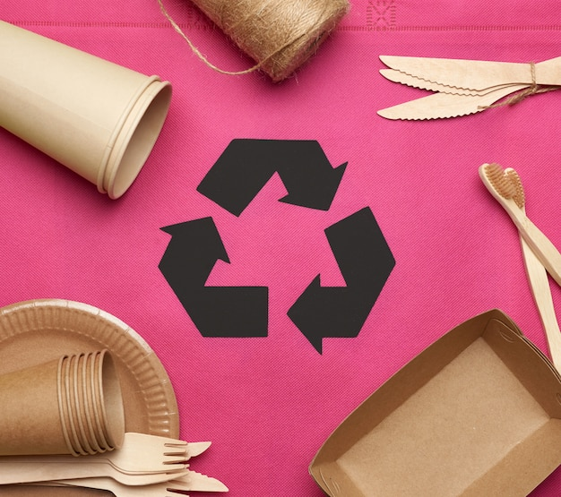 Disposable tableware from brown craft paper on a pink background