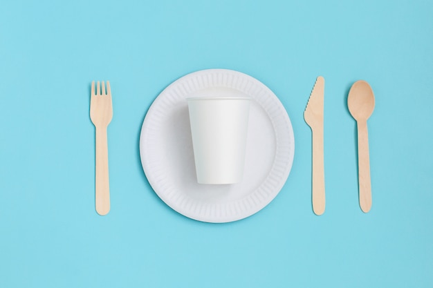 Disposable tableware from natural materials on blue background. eco-friendly