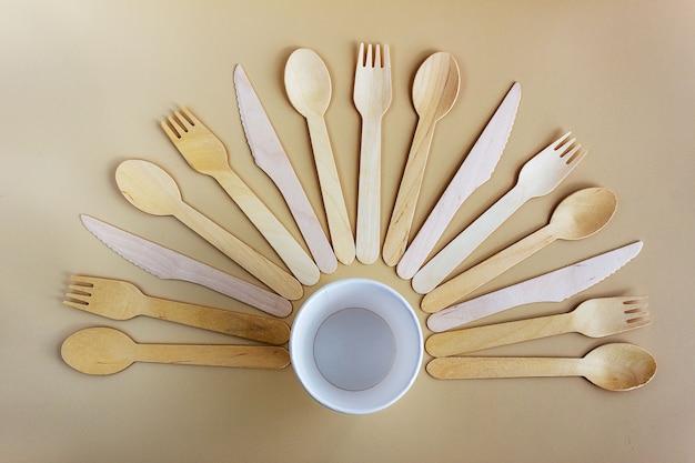 天然素材の使い捨て食器、木のスプーン、フォーク、ナイフ、紙コップ。生分解性のピクニック食器、プラスチックの最新の代替品。