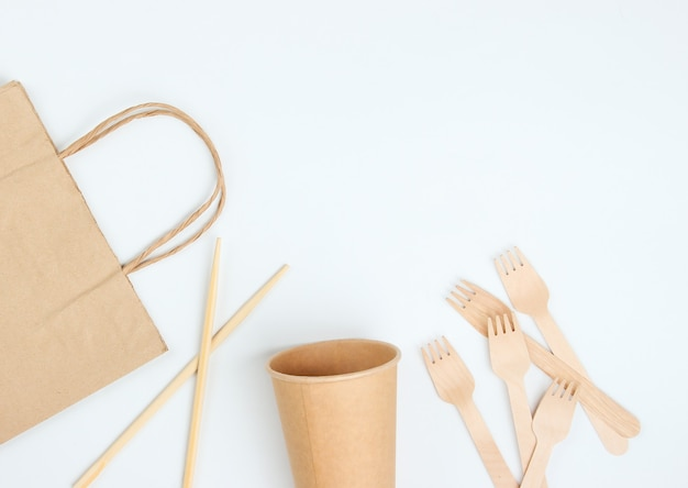 Disposable tableware of natural materials. eco friendly concept. wooden forks, empty craft coffee cup, bag, chopsticks on a white background.