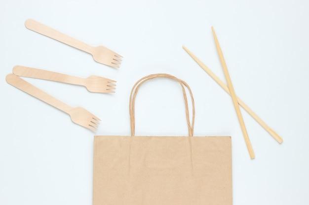 Одноразовая посуда из натуральных материалов. экологичная концепция. деревянные вилки, сумка, палочки для еды на белом фоне. вид сверху
