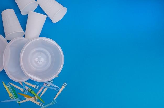 Одноразовая посуда на синем фоне. понятие: экология, загрязнение окружающей среды. изготовление блюд.