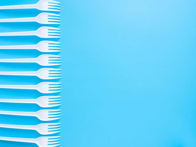 Disposable tableware, white plastic forks isolated on a blue background with copy space.