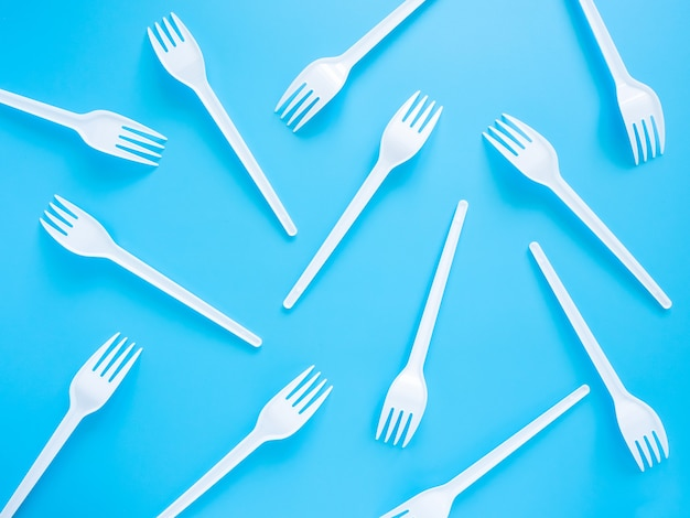 Disposable tableware, white plastic forks scattered on a blue background, top view, flat lay.