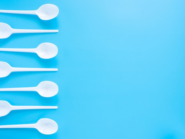 Disposable tableware, white plastic spoons isolated on a blue background with a copy of the space.