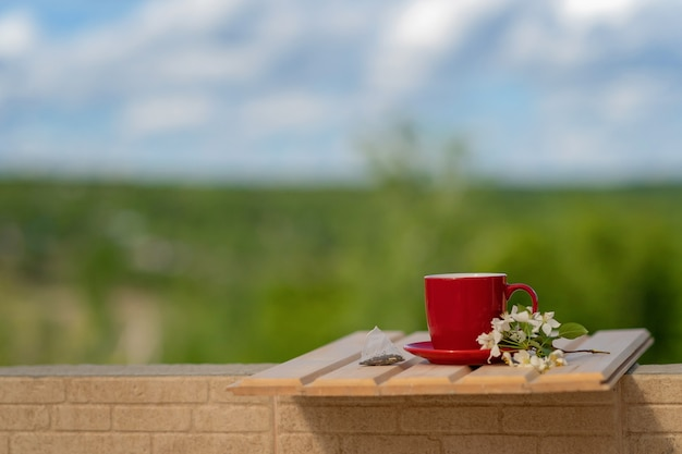 A disposable tea bag next to a red mug and a blossoming apple tree branch on a wooden table