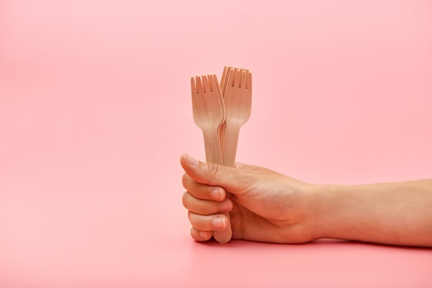 Disposable wooden cutlery forks in hand.