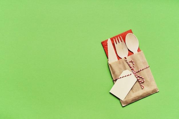 緑の色の背景のカトラリーのリサイクルと環境にやさしい紙袋の使い捨て木製カトラリー