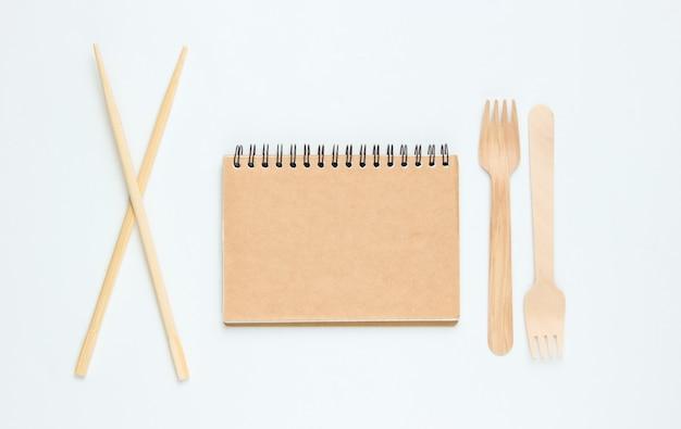 使い捨ての木製フォーク、クラフトトレシペノート、白い背景の上の箸。天然素材のカトラリー