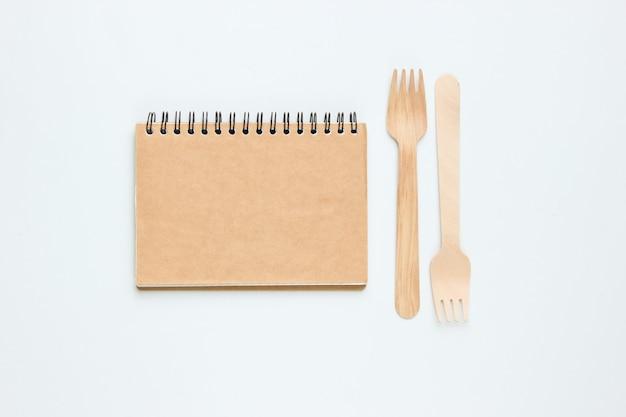 使い捨ての木製フォーク、白い背景の上のクラフトトレシペノートブック。天然素材のカトラリー