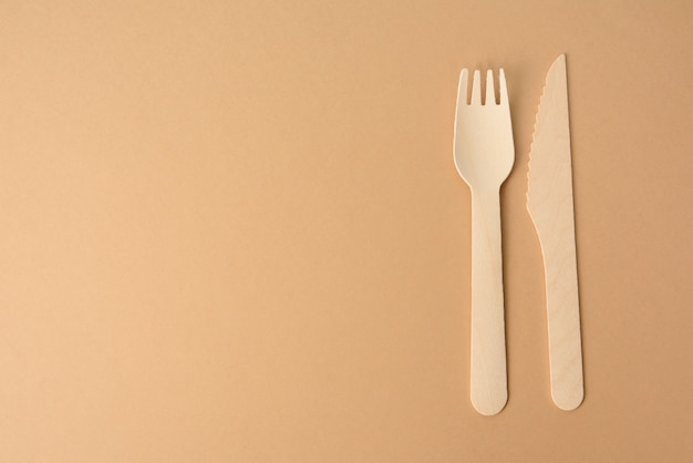 Disposable wooden forks and knife for fast food and picnic  on a brown background, copy space