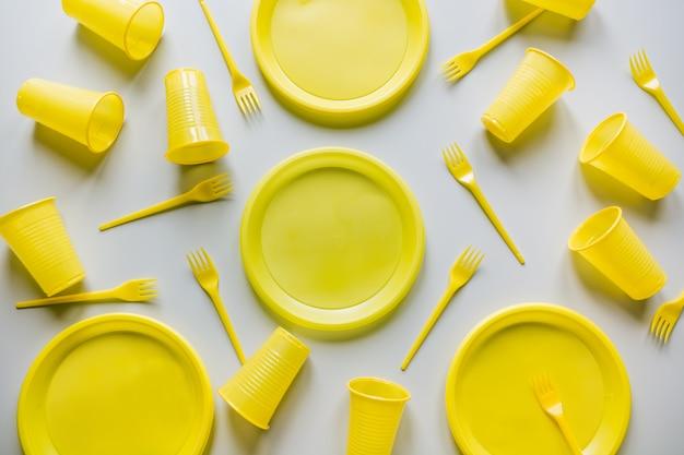 Одноразовые желтые посуда для пикника на сером.