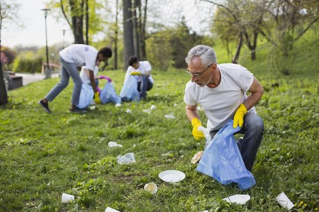Неуважение к природе. позитивный зрелый доброволец смотрит вниз и собирает мусор